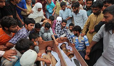 Kashmiris gather near the bodies of Muzaffar Bhat, left, and Fayaz Ahamed Wani  during their funeral procession in Srinagar, India, Tuesday, July 6, 2010. Government forces fired on hundreds of rock-throwing protesters in Indian Kashmir on Tuesday, killing Wani and wounding two others as a seven-day curfew was lifted, locals and officials said. Bhat was allegedly killed by paramilitary soldiers Monday.(AP Photo/Dar Yasin)