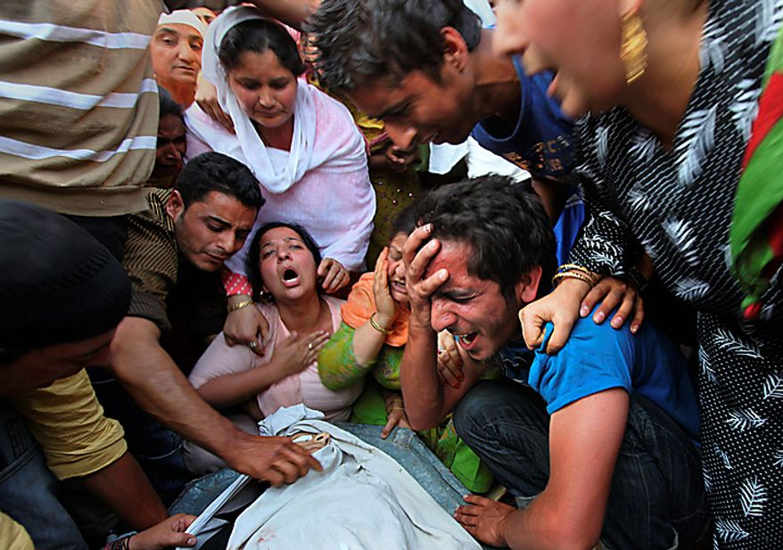 Relatives and neighbors grieve near the body of Abrar Khan during his funeral procession in Srinagar, India, Tuesday, July 6, 2010. Government forces fired on hundreds of rock-throwing protesters in Indian Kashmir on Tuesday, killing three and wounding two others as a seven-day curfew was lifted, locals and officials said. (AP Photo/Dar Yasin)