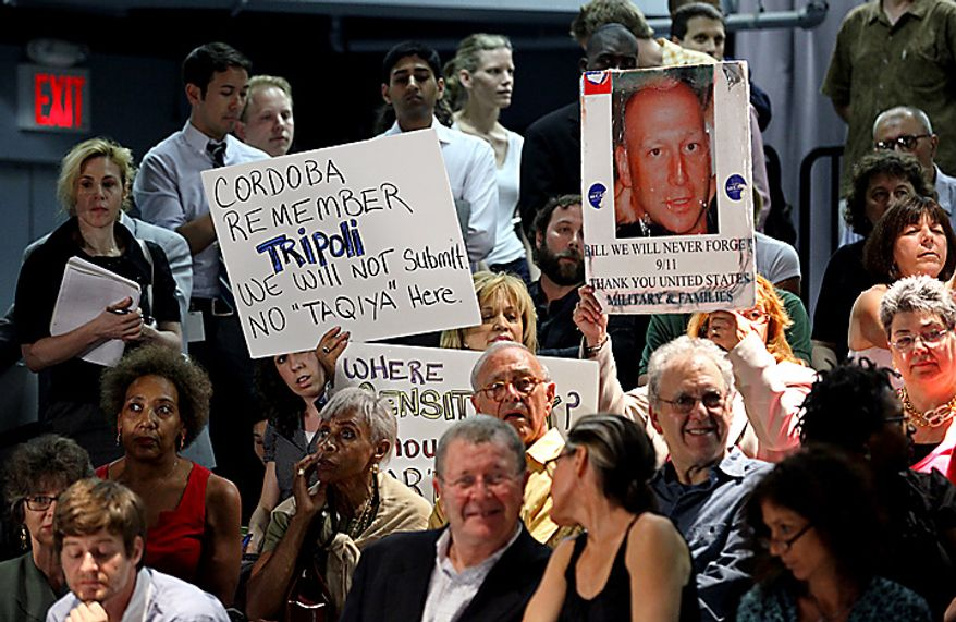 Members of the audience display signs as groups planning a proposed mosque and cultural center near Ground Zero in Lower Manhattan to be named Cordoba House showed and spoke about their plans for the center at a community board meeting in New York Tuesday, May 25, 2010. Community members both for and against the plan spoke during the meeting.  (AP Photo/Craig Ruttle)