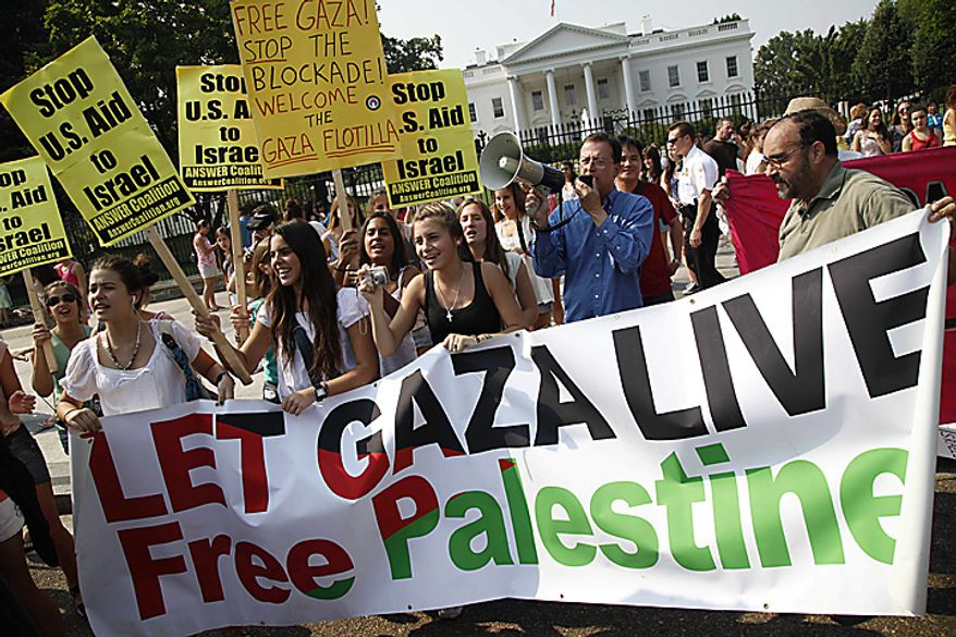 Tourists from Uruguay, left, hold up signs as they briefly join a protest against the meeting between President Barack Obama and Israeli Prime Minister Benjamin Netanyahu outside of the White House in Washington, Tuesday, July 6, 2010. (AP Photo/Charles Dharapak)