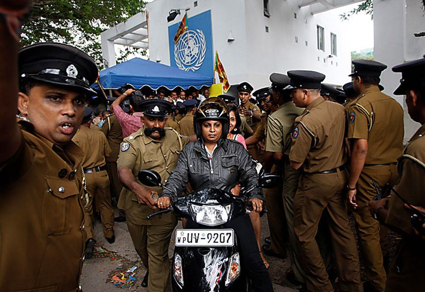 Sri Lankan police officials assist UN staffers to leave the UN office during a protest in Colombo, Sri Lanka, Tuesday, July 6, 2010. Police have broken up a blockade of the U.N. office in Sri Lanka's capital and are escorting employees out hours after they were trapped. (AP Photo/Eranga Jayawardena)