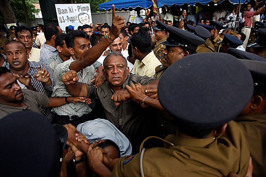 Sri Lankan protesters clash with police out side the UN office during a protest in Colombo, Sri Lanka, Tuesday, July 6, 2010. Police have broken up a blockade of the U.N. office in Sri Lanka's capital and are escorting employees out hours after they were trapped. (AP Photo/Eranga Jayawardena)
