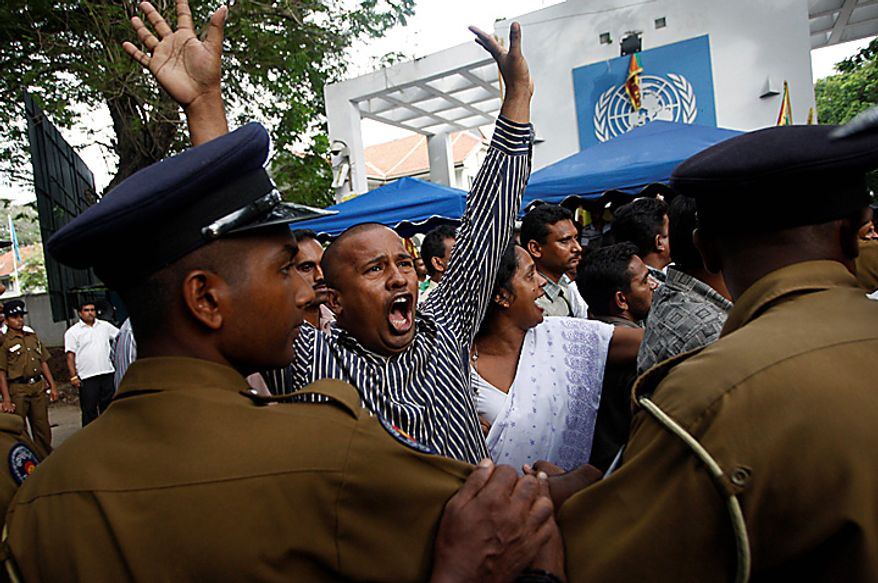 Sri Lankan protesters shout slogans as they clash with police outside the UN office during a protest in Colombo, Sri Lanka, Tuesday, July 6, 2010. Police have broken up a blockade of the U.N. office in Sri Lanka's capital and are escorting employees out hours after they were trapped. (AP Photo/Eranga Jayawardena)