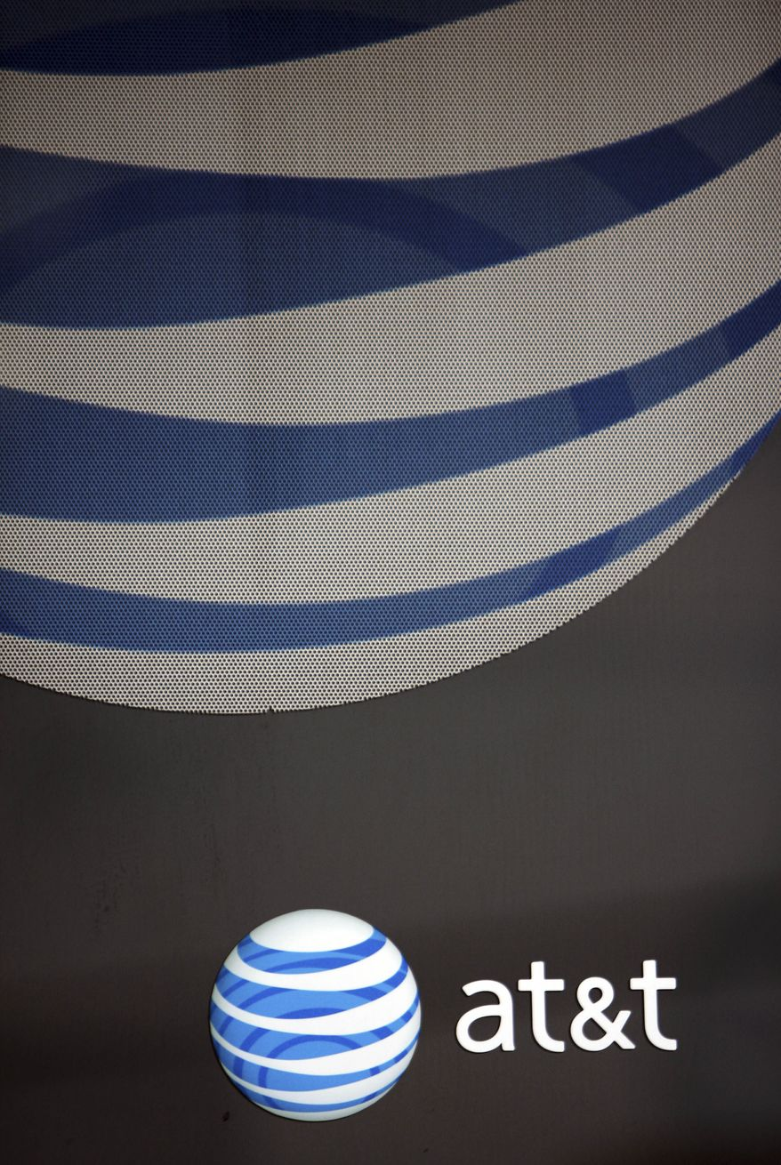 ** FILE ** In this file photo taken April 21, 2010, an AT&T logo and sign are seen on a window at a company store in Brunswick, Maine. AT&T said Wednesday, July 7, 2010, that a software glitch in network equipment made by Alcatel-Lucent is to blame for limiting the upload speeds of the iPhone 4. AT&T says a fix is in the works. (AP Photo/Pat Wellenbach, file)