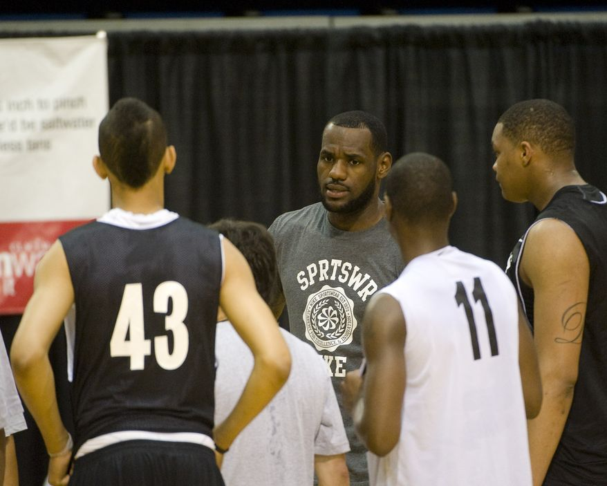 NBA free agent LeBron James talks with high school players at the LeBron James Skills Academy for high school and college basketball players at Rhodes Arena on the University of Akron campus in Akron, Ohio, Wednesday, July 7, 2010. (AP Photo/Phil Long)