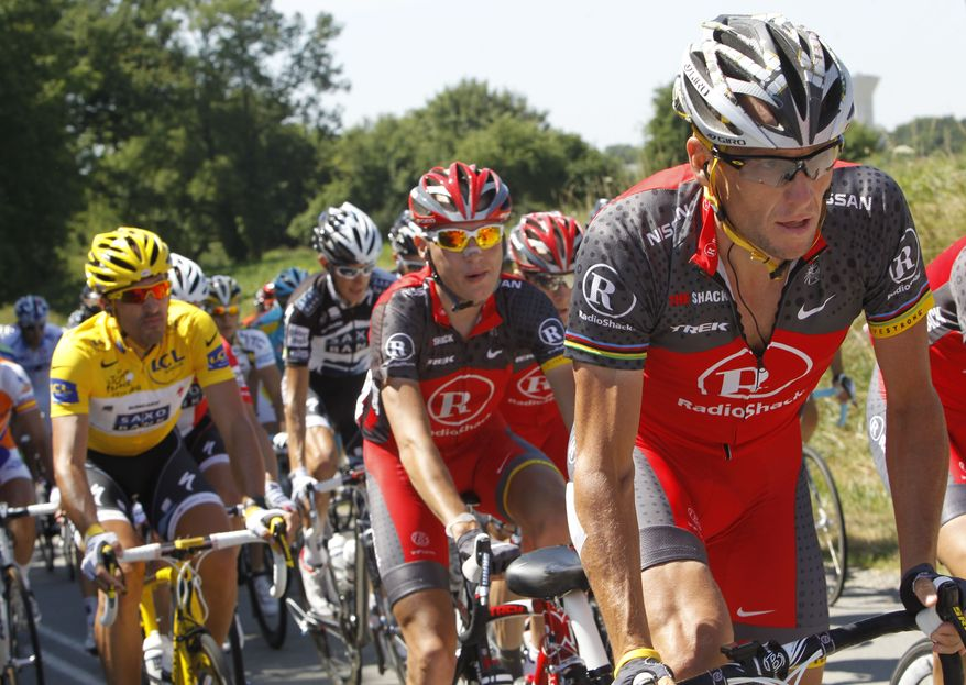 ASSOCIATED PRESS Lance Armstrong of the US, right, and Fabian Cancellara of Switzerland, wearing the overall leader's yellow jersey, left, ride in the pack during the fourth stage of the Tour de France cycling race over 153.5 kilometers (95.4 miles) with start in Cambrai and finish in Reims, northern France, Wednesday, July 7, 2010.