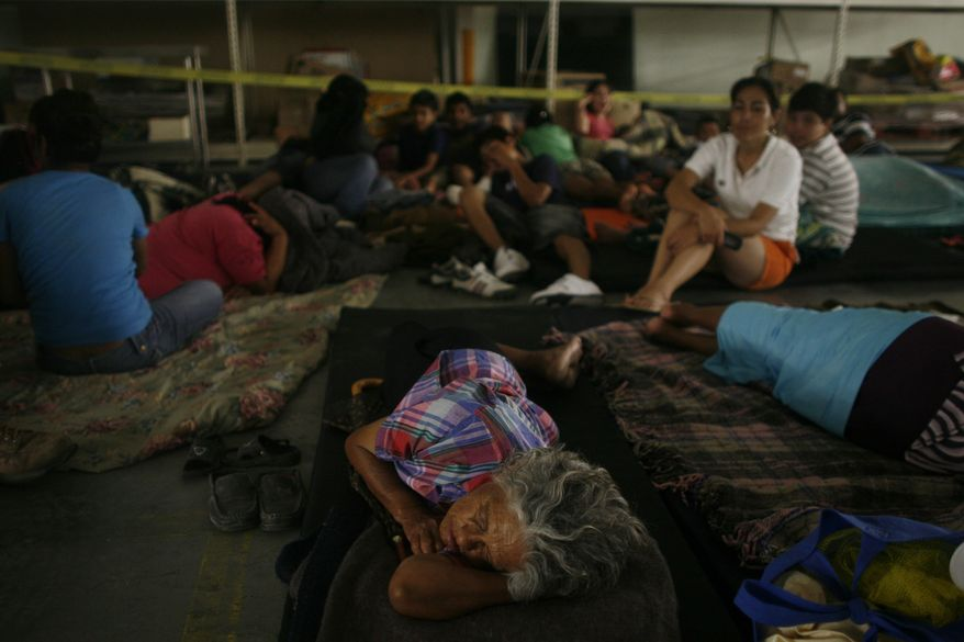 People rest on the floor of a warehouse in Nuevo Laredo, northeastern Mexico, after being evacuated from the nearby town of Ciudad Anahuac, Tuesday, July 6, 2010. About 18,000 people were evacuated Tuesday from Ciudad Anahuac where authorities opened a dam's floodgates for fear it would overflow from rains that accompanied Hurricane Alex. (AP Photo/Miguel Tovar)