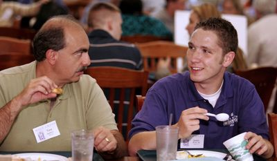 This undated photo provided by College of the Holy Cross shows parent Tony Squillaro, left, as he talks with orientation leader Justin Brooks in Kimball Dining Hall at the college in Worcester, Mass. Some orientations for families of incoming freshman are packed with workshops, tours and speeches on subjects ranging from letting go to campus safety. (AP Photo/College of the Holy Cross, Dan Vaillancourt)