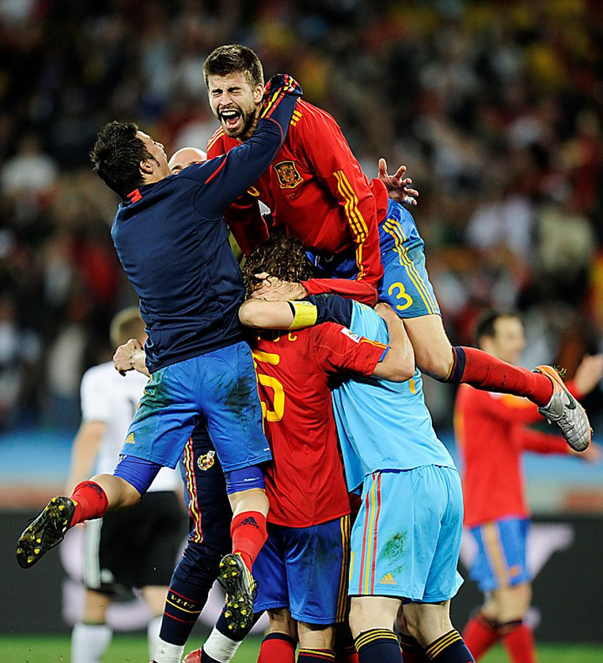 Spain's David Villa, left, Spain's Carles Puyol, second from left at bottom, Spain goalkeeper Iker Casillas, bottom right, and Spain's Gerard Pique, top right, celebrate following the World Cup semifinal soccer match between  Germany and Spain at the stadium in Durban, South Africa, Wednesday, July 7, 2010. Spain defeated Germany 1-0. (AP Photo/Martin Meissner)