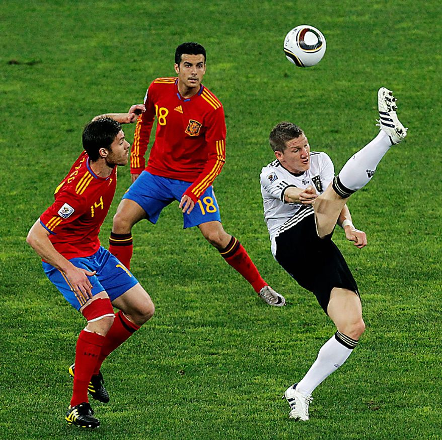 Germany's Bastian Schweinsteiger, right, kicks the ball as Spain's Xabi Alonso, left, as Pedro Rodriguez, center, looks on during the World Cup semifinal soccer match between  Germany and Spain at the Moses Mabhida stadium in Durban, South Africa, Wednesday July 7, 2010. (AP Photo/Themba Hadebe)