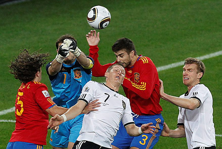 Spain goalkeeper Iker Casillas, second from left, punches away the ball from Germany's Bastian Schweinsteiger, bottom center, during the World Cup semifinal soccer match between  Germany and Spain at the Moses Mabhida stadium in Durban, South Africa, Wednesday July 7, 2010. (AP Photo/Themba Hadebe)