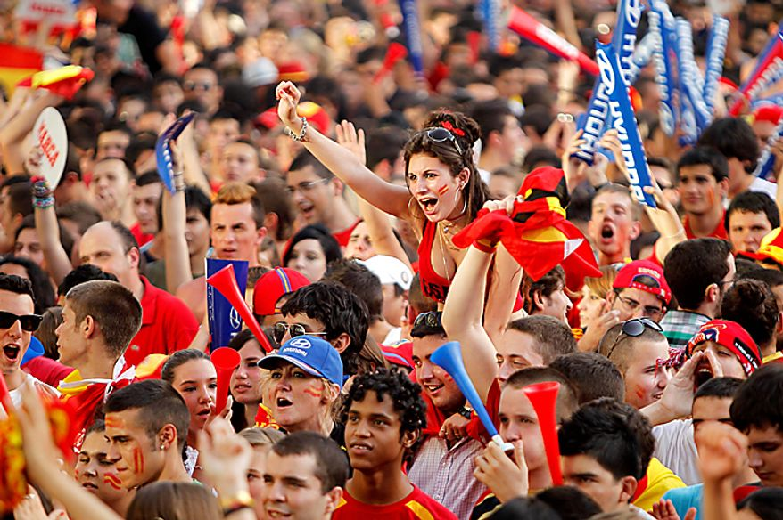 Soccer fans react before the start of the World Cup semifinal soccer match between Spain and Germany shown on a large screen outside the Santiago Bernabeu stadium in Madrid, on Wednesday, July 7, 2010. (AP Photo/Paul White)