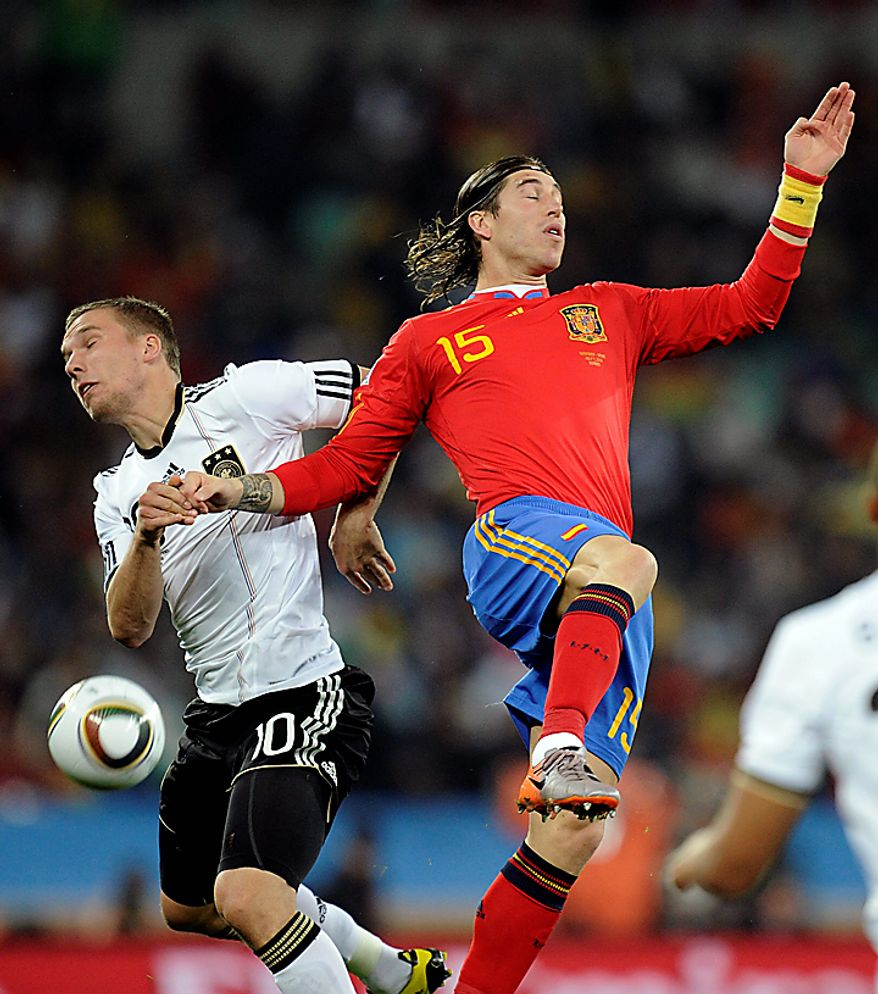 Germany's Lukas Podolski, left, and Spain's Sergio Ramos fight for the ball during the World Cup semifinal soccer match between  Germany and Spain at the stadium in Durban, South Africa, Wednesday, July 7, 2010.  (AP Photo/Martin Meissner)