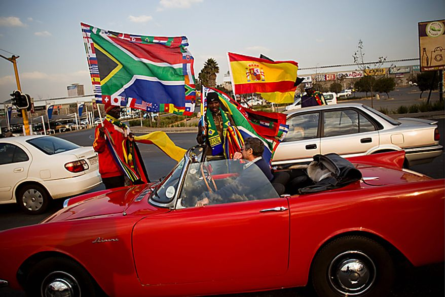Street vendors try to sell flags and other items in a street of Johannesburg, South Africa, Wednesday, July 7, 2010. The final match of the first soccer World Cup in the African continent will be played on Sunday, July 11. (AP Photo/Bernat Armangue)