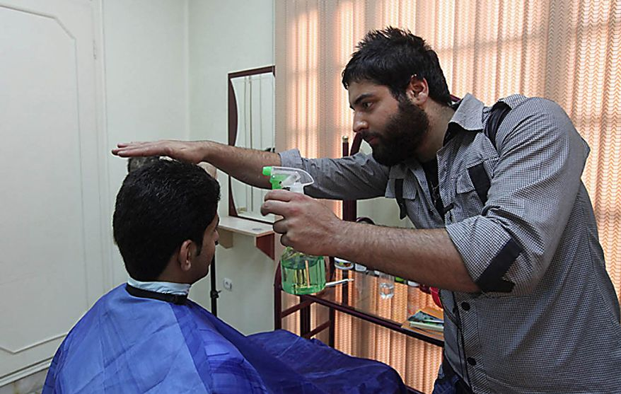 In this picture released by the semi-official Iranian Mehr News Agency, a barber cuts hair in an official hairdressing show for men culturally appropriated by the Iran's Ministry of Culture and Islamic Guidance, in Tehran, Iran, on Monday, July 5, 2010. An Iranian fashion organization has issued a new list of culturally appropriate haircuts for men, possibly indicating a new crackdown on male attire after years of strict rules for women, Iranian media reported. (AP Photo/Mehr News Agency, Mohsen Rezaei/HO)