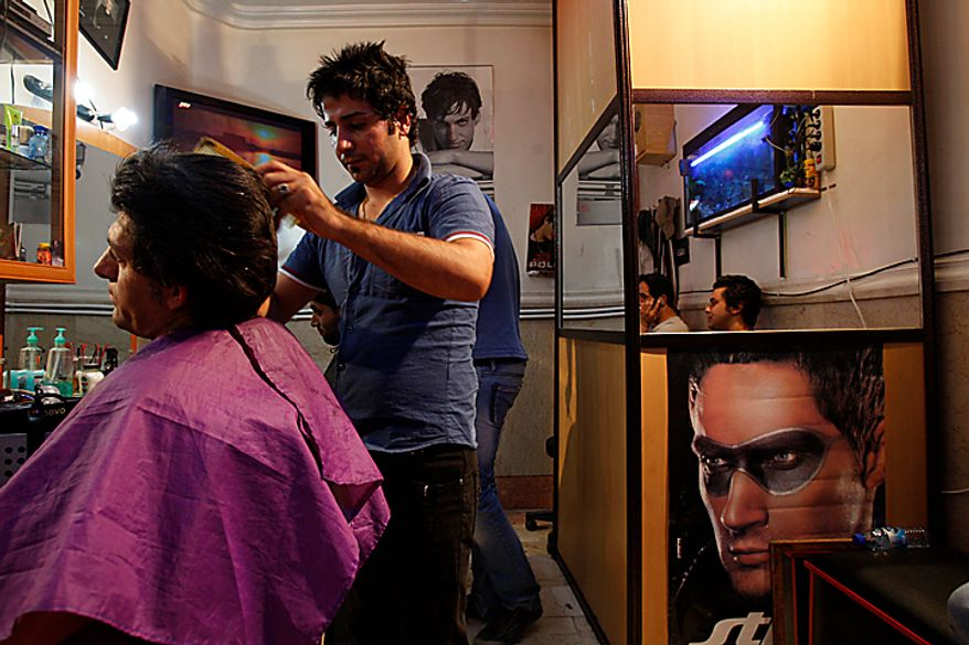 An Iranian barber cuts hair in his barber shop in midtown Tehran, Iran, Wednesday, July 7, 2010. An Iranian fashion organization has issued a new list of culturally appropriate haircuts for men, possibly indicating a new crackdown on male attire after years of strict rules for women, Iranian media reported. (AP Photo/Vahid Salemi)