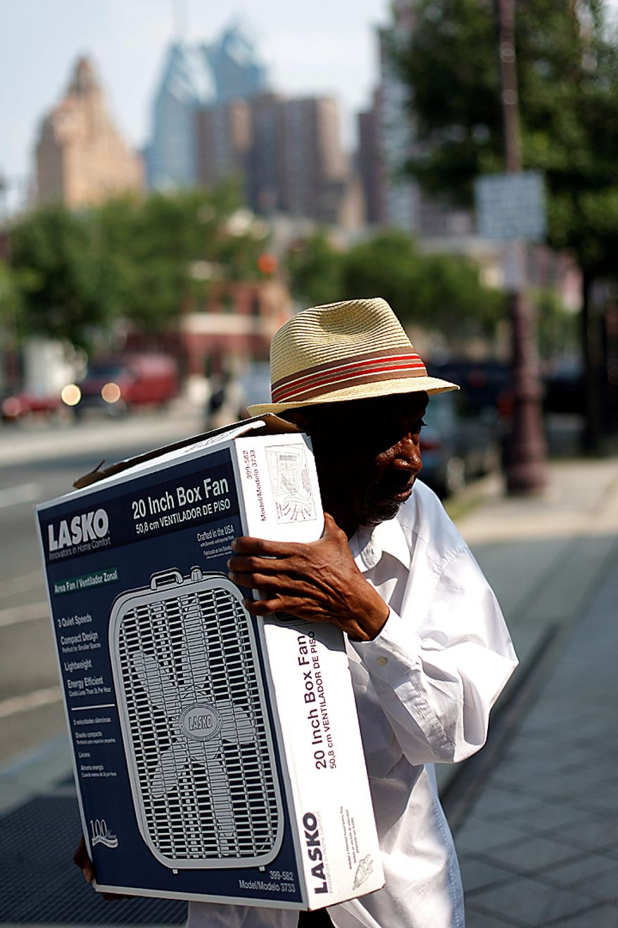 Joseph Moore, 80, carries a fan donated by the Comcast-Spectacor Foundation and distributed at the Philadelphia Senior Center in Philadelphia, Wednesday, July 7, 2010.  Heat and humidity draped the Northeast for yet another day Wednesday, pushing electric utilities to crank up power and keeping the mercury expected to hover around 100 from Virginia to New Hampshire. (AP Photo/Matt Rourke)