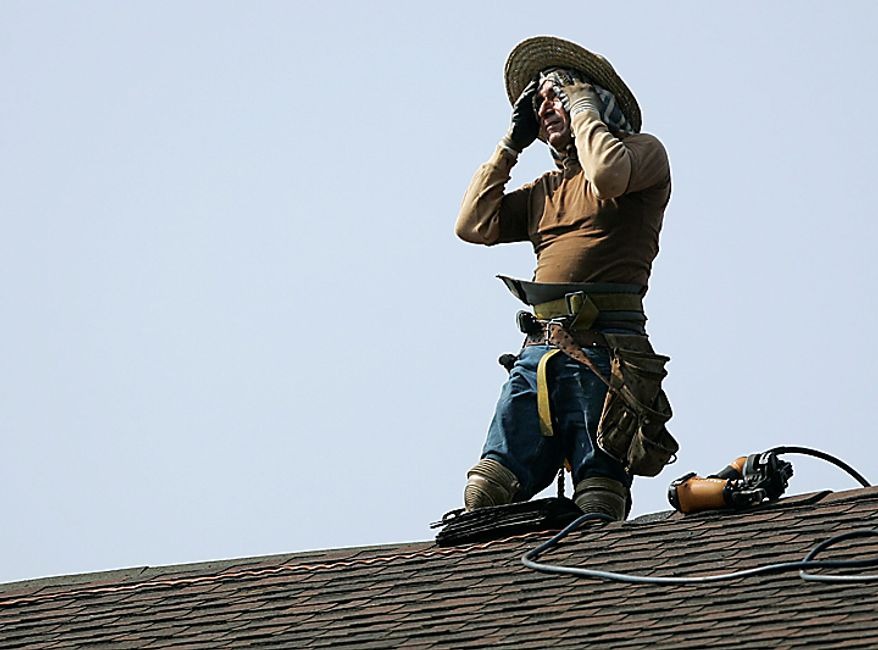 A construction worker wipes sweat from his face as he installs roofing tiles as part of a solar panel installation project at Park Ridge High School in Park Ridge, N.J., Wednesday, July 7, 2010. Temperatures in the Northeast are expected to reach 100 for the second straight day. (AP Photo/Rich Schultz)