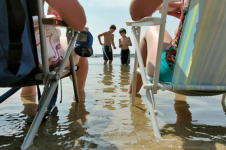 In this Tuesday, July 6, 2010 photo, Tyler Troiano, 12, center left, and friend Joey Reis,10, look for periwinkles on Onset Beach in Wareham, Mass., as Karen Calhoun, left, and Tyler's mom Angela Troiano, right, enjoy the cool water.  (AP Photo/The Standard Times, Peter Pereira)