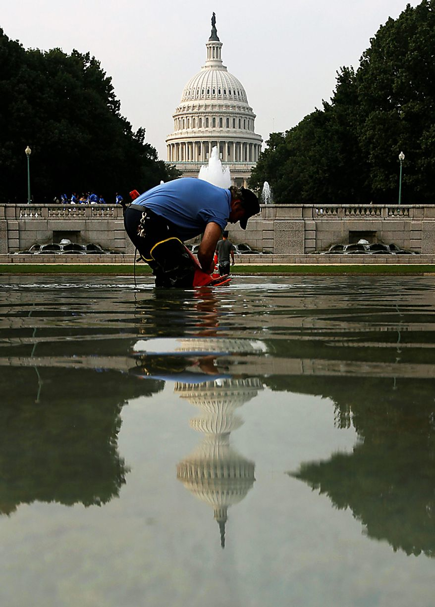 Mark Wooldridge, with the Architect of the Capitol Grounds Crew, work on the drains in the reflecting pool on the Senate side of the Capitol in Washington Wednesday, July 7, 2010. The pool is cleaned and checked frequently to get the debris out of it. (AP Photo/Alex Brandon)