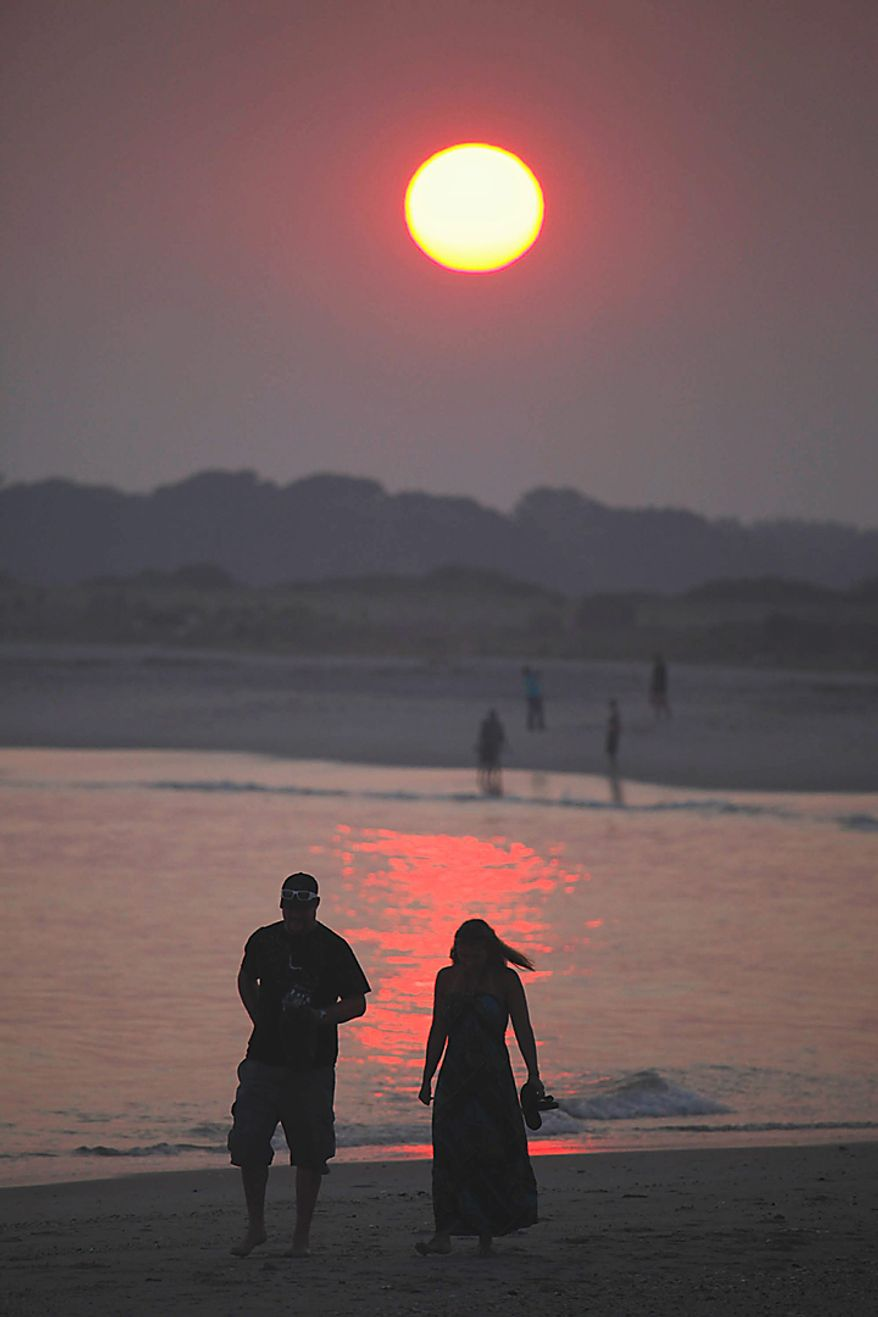 People gather along Cape May Beach on Tuesday, July 6, 2010, in Cape May, N.J. to watch the sunset. The East Coast broiled under an unforgiving sun Tuesday as record-toppling temperatures soared to 100 or higher in several cities, utility companies cranked out power to cool the sweating masses and the unlucky sought any oasis they could find.  (AP Photo/Tim Donnelly)