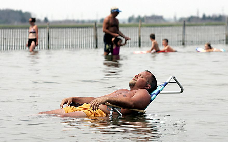 David Augustane, a Ship Bottom, homeowner cools off in the bay in Ship Bottom, N.J. on Tuesday July 6, 2010.  (AP Photo/The Press of Atlantic City, Bill Gross)