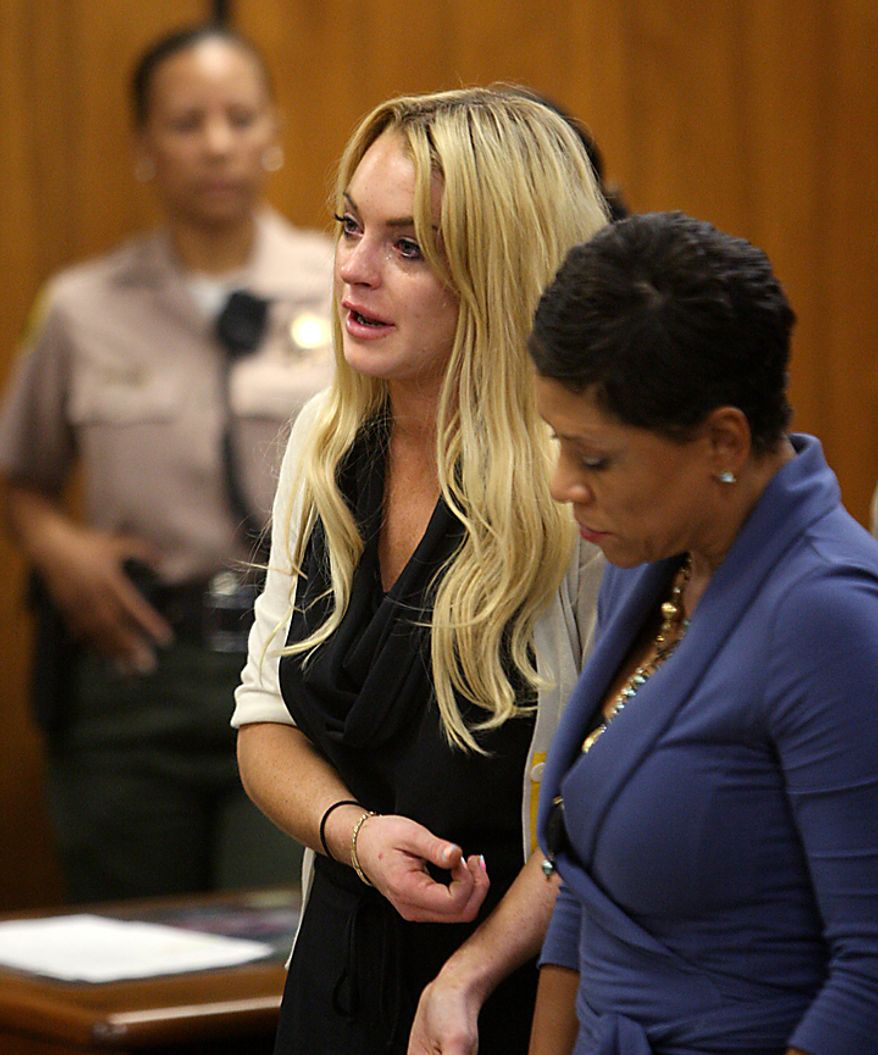 Actress Lindsay Lohan (L) reacts with her attorney Shawn Chapman Holley following her sentencing by Superior Court Judge Marsha Revel during a probation status hearing in Beverly Hills, California on July 6, 2010. Revel sentenced Lohan to 90 days in jail Tuesday after ruling she violated probation in a 2007 drug case by failing to attend court-ordered alcohol education classes.    UPI/David McNew/Pool
