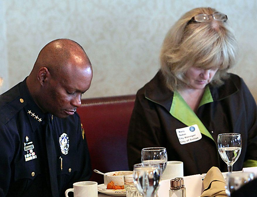 Dallas Police Chief David Brown and Dallas City Manager Mary Suhm, right, bow their heads in prayer during a breakfast meeting Wednesday July 7, 2010 of the North Texas Crime Commission at the Park Cities Club, in Dallas. Brown is resuming his public duties more than two weeks after his son was killed. An autopsy found that David Brown Jr. had marijuana and PCP in his system when he fatally shot Lancaster police Officer Craig Shaw and neighbor Jeremy McMillan on June 20. The Father's Day shootings took place during a domestic dispute at an apartment complex. Officers returned fire and killed Brown Jr. (AP Photo/The Dallas Morning News, Jim Mahoney)