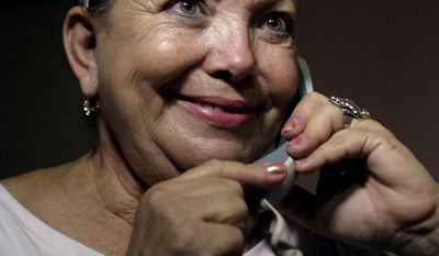 Laura Pollan speaks with hospitalized dissident Guillermo Farinas on the phone after Cuba's Roman Catholic Church said that the government has agreed to free 52 political prisoners and allow them to leave the country in Havana on Wednesday, July 7, 2010. Ms. Pollan is the leader of Ladies in White, an organization made up of wives and mothers of political prisoners, and her husband Hector Maseda is one of the 52 people expected to be released. (AP Photo/Franklin Reyes)