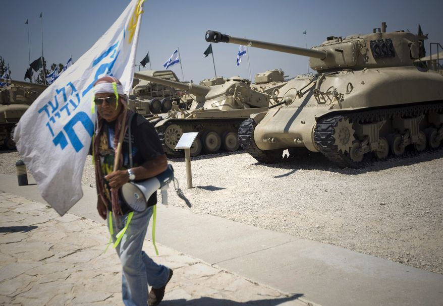 """An Israeli man walks past tanks on display in the Armored Corps Memorial and Museum near Jerusalem during a rally in support of a captured Israeli soldier Gilad Schalit on Wednesday, July 7, 2010. Text on flag reads in Hebrew: """"Gilad is still alive."""" (AP Photo/Ariel Schalit)"""