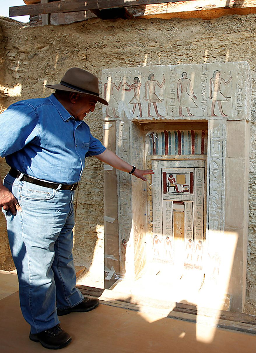 Egyptian Antiquities chief Zahi Hawass shows to the media the false door of the unearthed tomb that belongs to Shendwas, the father of Khonsu, both of whom served as heads of the royal scribes during the Old Kingdom, in Saqqara near Cairo, Egypt, Thursday, July 8, 2010. Egyptian archaeologists have unveiled their latest discovery - two 4,300-year-old tombs carved out of stone and unearthed in the ancient necropolis of Saqqara near Cairo. (AP Photo/Nasser Nasser)