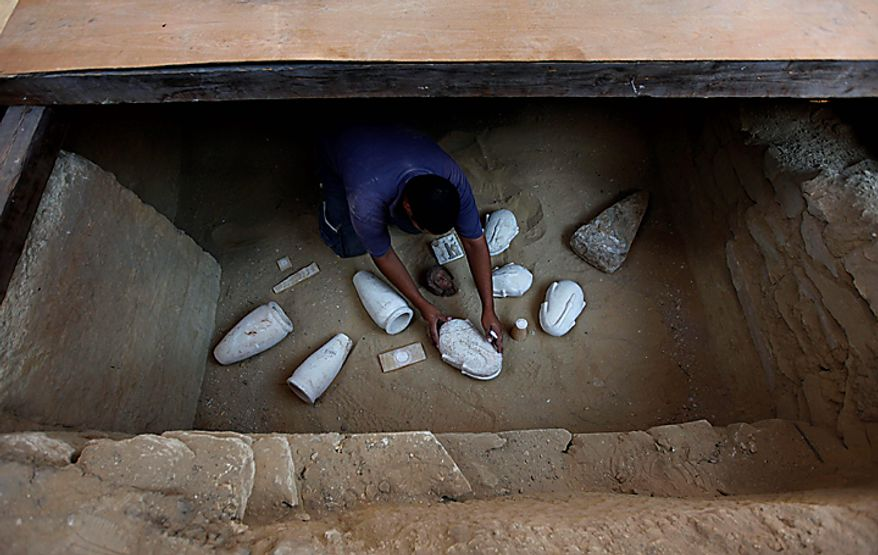 An Egyptian Antiquities worker displays funeral artifacts recovered from the unearthed 4,300-year-old tombs of Khonsu and his father Shendwas, both of whom served as heads of the royal scribes during the Old Kingdom, in Saqqara near Cairo, Egypt, Thursday, July 8, 2010. (AP Photo/Nasser Nasser)
