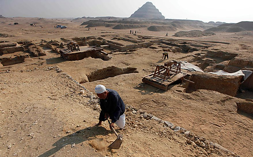 With the Step Pyramid of King Djoser in the background, an Egyptian laborer works at the site of the unearthed 4,300-year-old tombs of Khonsu and his father Shendwas, both of whom served as heads of the royal scribes during the Old Kingdom, in Saqqara near Cairo, Egypt, Thursday, July 8, 2010. Egyptian archaeologists have unveiled their latest discovery - two 4,300-year-old tombs carved out of stone and unearthed in the ancient necropolis of Saqqara near Cairo. (AP Photo/Nasser Nasser)