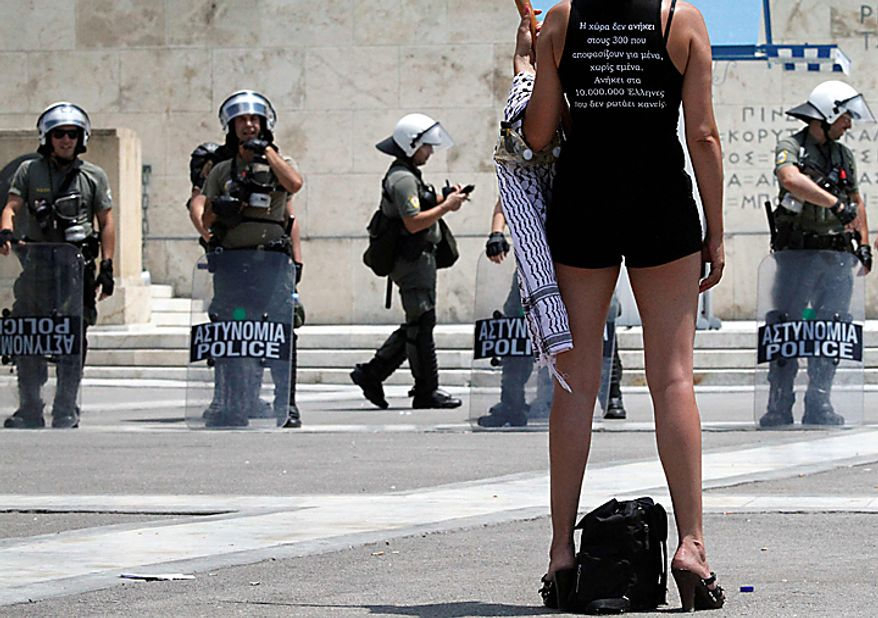 """A protester stands in front of riot police outside parliament during a rally in central Athens, Thursday, July 8, 2010. More than 12,000 people took part in two separate protest marches, according to police estimates. Greece's governing Socialists are battling growing discontent as a new round of economic austerity faces party dissent, growing public hostility and fresh strike. The slogan on the T-shirt reads: """"This country does not belong to the 300 (members of parliament) but the 10 million Greeks.""""  (AP Photo/Dimitri Messinis)"""