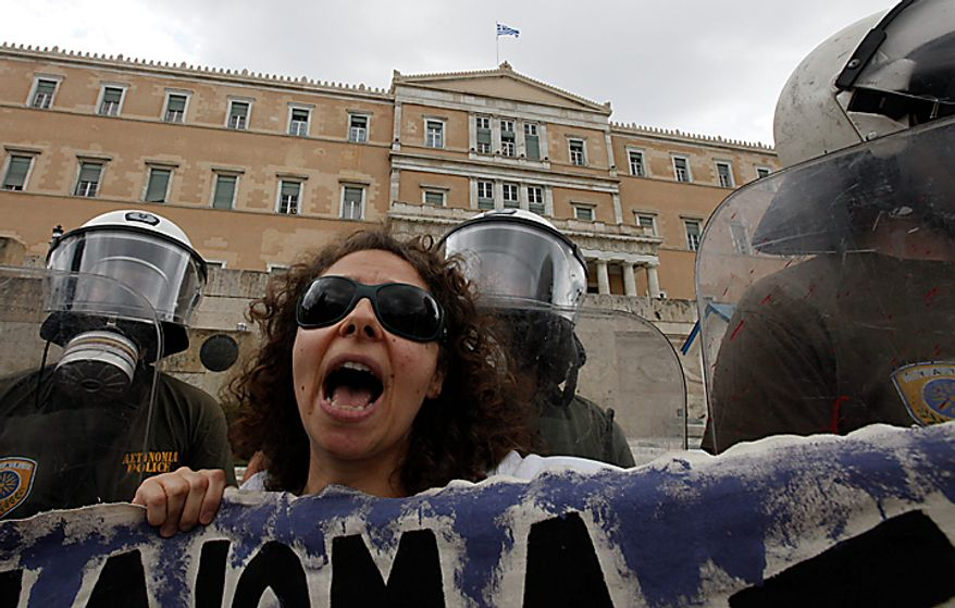 A protester shouts slogans in front of riot police outside parliament during a rally in central Athens, Thursday, July 8, 2010. More than 12,000 people took part in two separate protest marches, according to police estimates. Greece's governing Socialists are battling growing discontent as a new round of economic austerity faces party dissent, growing public hostility and fresh strike. (AP Photo/Dimitri Messinis)
