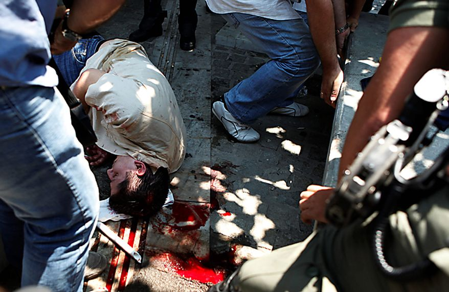 A man lies injured in the street after being assaulted by violent demonstrators during a protest in  central Athens, Thursday, July 8, 2010. Authorities identified the man as a public servant who was apparently wrongly identified as a plain clothed policeman. More than 12,000 people took part in two separate protest marches, according to police estimates. Greece's governing Socialists are battling growing discontent as a new round of economic austerity faces party dissent, growing public hostility and fresh strike. (AP Photo/Evi Zoupanou)