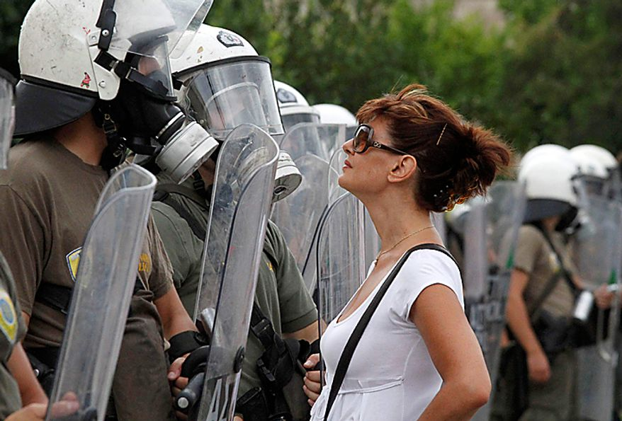 A protester confronts riot police outside parliament during a rally in central Athens, Thursday, July 8, 2010. The Greek government is battling growing discontent over a new round of economic austerity, with fresh strikes, public hostility, and party dissent testing the nation's ability to make it out of its debt crisis. Unions on Thursday staged their sixth general strike this year _ halting public transport and services, stopping ferry departures and closing schools, newspapers, courts and public hospitals.  (AP Photo/Dimitri Messinis)