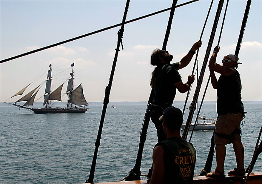 """Crewmen on the HMS Bounty trim their sails as the USS Niagara sails past on Lake Erie off Cleveland Wednesday, July 7, 2010. The Bounty, built for the 1961 movie """"Mutiny on the Bounty,"""" is one of 11 tall ships that will be in the city for a weekend festival. (AP Photo/Mark Duncan)"""