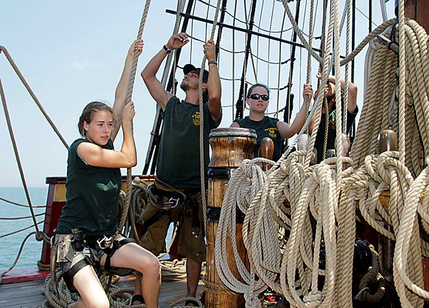 """Crew members hoist the sails on the HMS Bounty on Lake Erie off Cleveland, Wednesday, July 7, 2010. The sailing ship, built for the 1961 movie """"Mutiny on the Bounty,"""" is one of 11 tall ships that will be in the city for a weekend festival. (AP Photo/Mark Duncan)"""