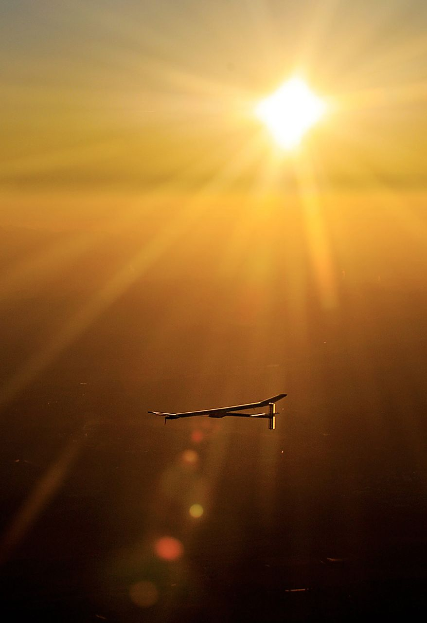 Solar Impulse's Chief Executive Officer and pilot Andre Borschberg flies in the solar-powered HB-SIA prototype airplane after its first night flight attempt near Payerne airport, Switzerland, as the sun rises, Thursday, July 8, 2010. The experimental solar-powered plane landed safely after completing its first 24-hour test flight. The record feat brings it one step closer to the makers' ultimate aim of circling the globe using only energy from the sun.(AP Photo/Keystone/Fabrice Coffrini/Pool)