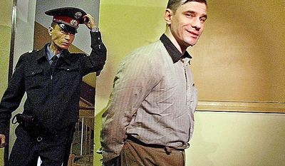In this Monday, Sept. 2, 2002, file photo a policeman escorts Russian arms control analyst Igor Sutyagin, accused of spying for the United States, to a courtroom in Moscow. A lawyer for  Sutyagin said Thursday, July 8, 2010, he reportedly has been flown to Vienna in what appeared to be the first step of a Russia-U.S. spy swap. (AP Photo/Maxim Marmur, File)