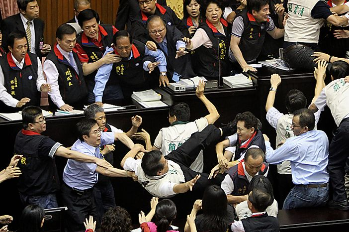Ruling and opposition lawmakers brawl as discussions start on the Economic Cooperation Framework Agreement (ECFA) planned with China on the legislature floor on Thursday, July 8, 2010, in Taipei, Taiwan. Pro-and anti-government lawmakers exchanged punches and threw garbage bins at each other Thursday in another raucous session in Taiwan's legislature after the speaker rejected an opposition bid to conduct a detailed debate on a contentious trade pact with China. (AP Photo/Wally Santana)