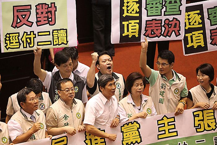 """Opposition lawmakers chant slogans and hold placards denouncing the Economic Cooperation Framework Agreement (ECFA) planned with China on the legislature floor as legislatures start a review of the ECFA, Thursday, July 8, 2010, in Taipei, Taiwan. Opposition legislators chanted anti-trade pact slogans as they protested the planned trade agreement with rival China, saying it will undermine the island's self-rule and its economy. The placards read, """"Review the trade deal piece by piece, not as a whole package."""" (AP Photo/Wally Santana)"""