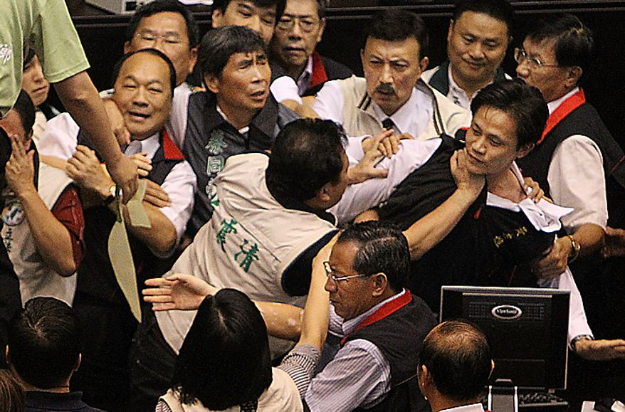Ruling, red collar and opposition lawmakers brawl as discussions start on the Economic Cooperation Framework Agreement (ECFA) planned with China on the legislature floor, Thursday, July 8, 2010, in Taipei, Taiwan. Pro-and anti-government lawmakers exchanged punches and threw garbage bins at each other Thursday in another raucous session in Taiwan's legislature after the speaker rejected an opposition bid to conduct a detailed debate on a contentious trade pact with China. (AP Photo/Wally Santana)