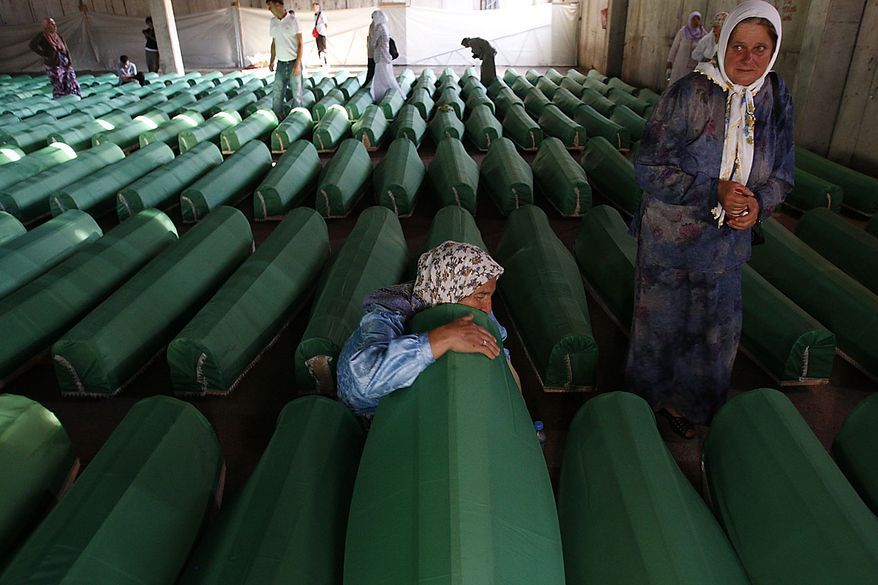 A Bosnian Muslim woman touches coffin of her son among coffins of Srebrenica victims displayed at the memorial center of Potocari near Srebrenica, 120 kms northeast of Sarajevo on Friday, July 9, 2010. The 775 bodies were excavated from mass-graves in Eastern Bosnia and were identified as Muslims killed by Bosnian-Serb forces in the Srebrenica area. Bosnian Serb troops massacred up to 8,000 Bosnian Muslim men after capturing Srebrenica on July 11, 1995, during the 1992-1995 war in Bosnia-Herzegovina. The 775 identified victims will be buried on July 11 in the Memorial Center Potocari. (AP Photo/Amel Emric)