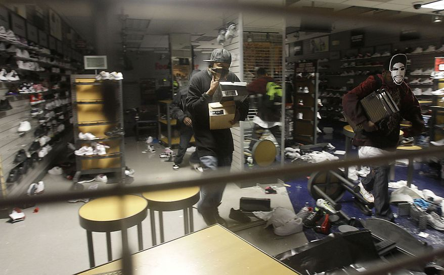 Unidentified people loot a Foot Locker store in Oakland, Calif., following an involuntary manslaughter verdict in Johannes Mehserle's trial on Thursday, July 8, 2010. A white former San Francisco Bay Area Rapid Transit police officer, Mehserle was found guilty of involuntary manslaughter in Los Angeles for shooting unarmed black man Oscar Grant on New Year's Day 2009 at a BART station in Oakland. (AP Photo/Jeff Chiu)