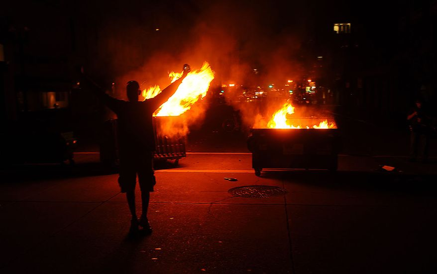 A man celebrates as dumpsters burn in Oakland, Calif., following an involuntary manslaughter verdict in Johannes Mehserle's trial on Thursday, July 8, 2010. A former transit police officer, Mehserle shot and killed unarmed black man Oscar Grant on New Year's Day 2009. (AP Photo/Noah Berger)