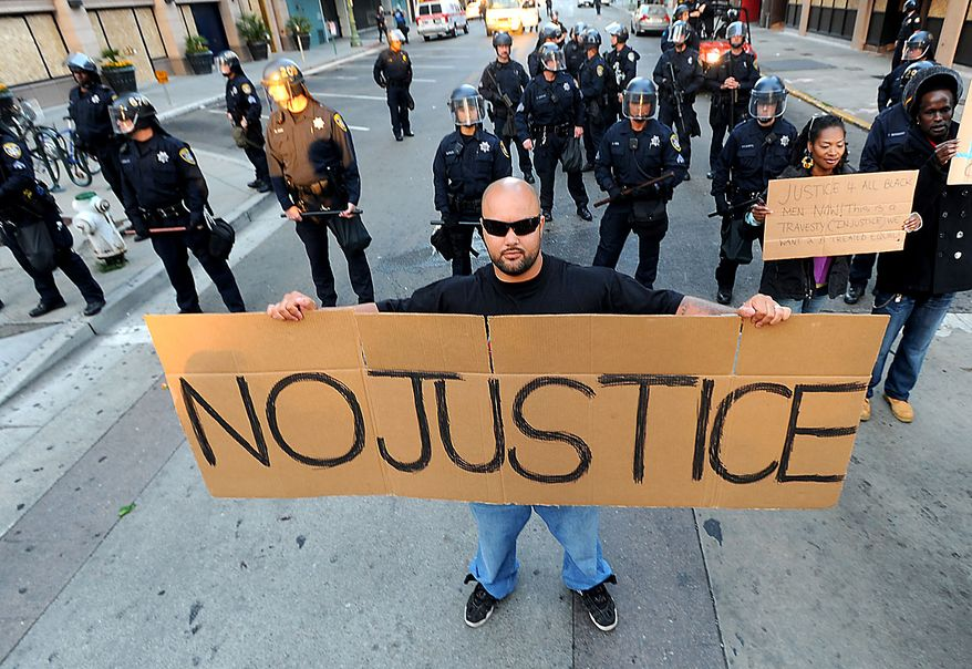 John Lopes protests in Oakland, Calif., following an involuntary manslaughter verdict in Johannes Mehserle's trial on Thursday, July 8, 2010. A former transit police officer, Mehserle shot and killed unarmed black man Oscar Grant on New Year's Day 2009.  (AP Photo/Noah Berger)