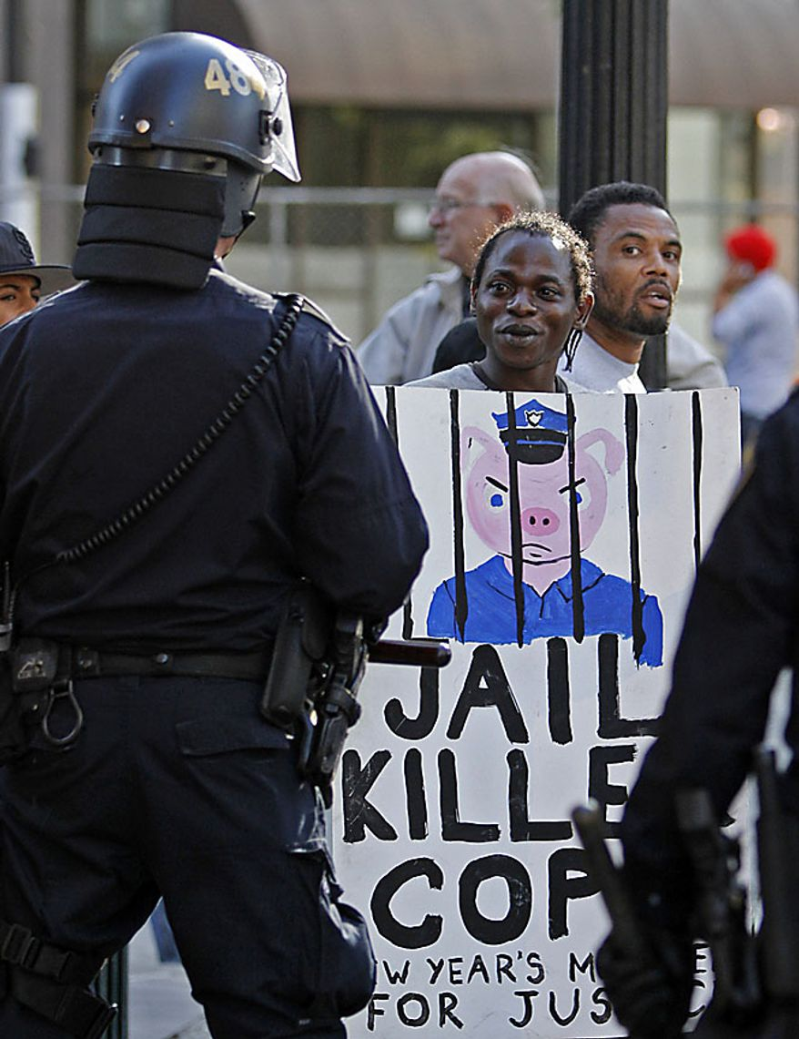 A protester taunts policemen during a protest of the verdict of involuntary manslaughter given to Johannes Mehserle Thursday, July 8, 2010, in Oakland, Calif. Former Bay Area Rapid Transit police officer Johannes Mehserle was found guilty in Los Angeles for shooting unarmed black man Oscar Grant on New Year's Day 2009 at a BART station in Oakland. (AP Photo/Ben Margot)