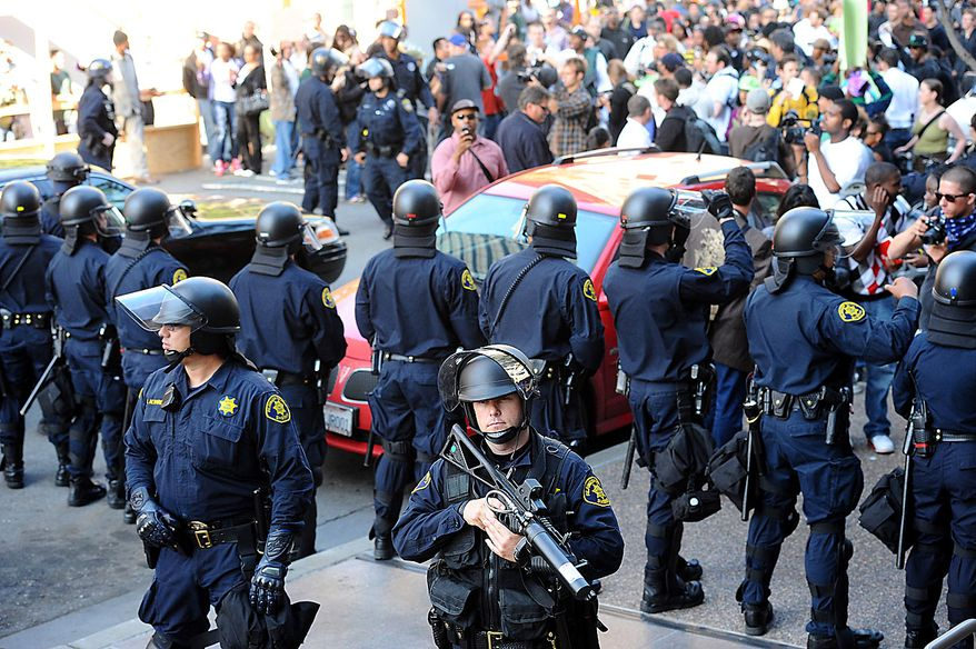 Police hold back protesters in Oakland, Calif., following an involuntary manslaughter verdict in Johannes Mehserle's trial on Thursday, July 8, 2010. A former transit police officer, Mehserle shot and killed unarmed black man Oscar Grant on New Year's Day 2009.  (AP Photo/Noah Berger)